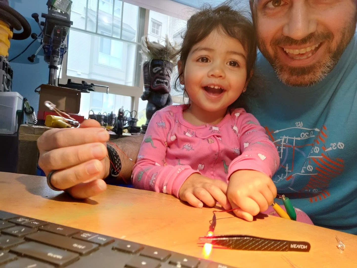 Little one helping make the LED glowing embers for the wig